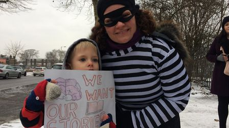 A protester and her son outside the library. Picture: JON KING