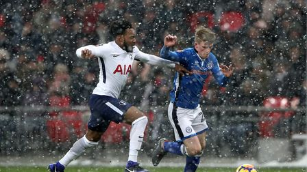 Tottenham Hotspur's Danny Rose (left) and Rochdale's Andy Cannon battle for the ball as the snow fal