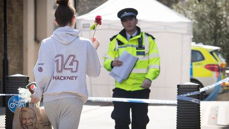 A woman brings a flower to the scene of Israel Ogunsola's stabbing in Link Street, off Morning Lane,