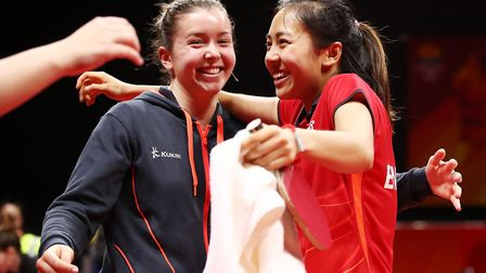 Tin-Tin Ho of England celebrates with Denise Payet after beating Canada in the Women's team table te