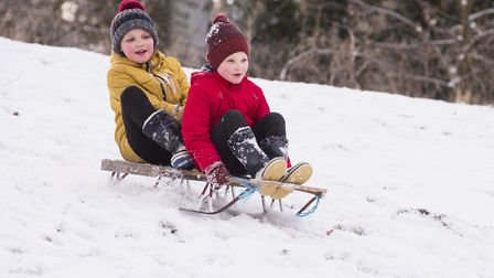 Charlie (yellow) and Isaac Bullion from Beccles enjoy the snow before school. Picture: Nick Butcher