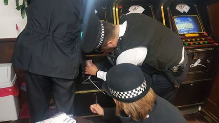 Police seizing the gambling machines. Picture: Hackney Council
