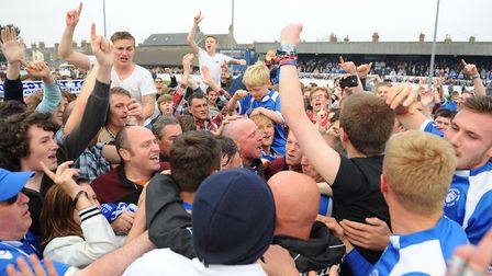 The highs - management, players and fans on the pitch celebrating promotion. Picture: James Bass