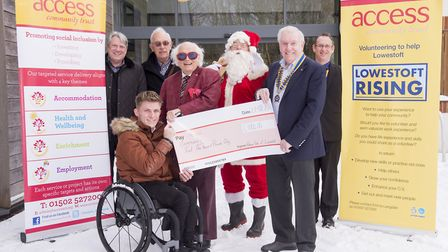 Joel Connor-Saunders, supported volunteer for Access Community Trust, recieves a cheque from members