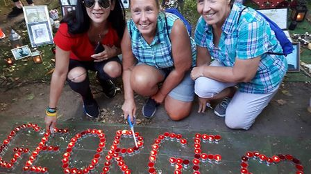 A group of George Michael fans pay tribute at a candlelit event marking the final days of the garden