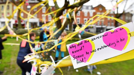 Ribbons, jokes, hand-made flowers and painted stones are added to a tree in Fortune Green in West Ha