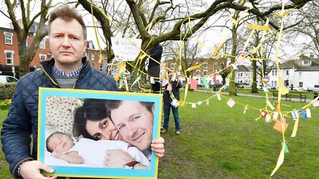 Richard Ratcliffe holds a photograph of himself with wife Nazanin and daughter Gabriella, in front o