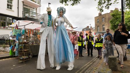 The two stilt walkers at the fair, as a child looks on