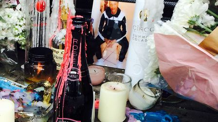 A photo of Rashan Charles among flowers laid outside Yours Locally in Kingsland Road following his d