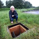 Resident and park user mary Russell next to the open manhole, left without a cover, on the grass at
