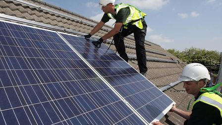 Workmen installing solar panels similar to those on Muswell Hill Methodist Church. Picture: SIMON BU