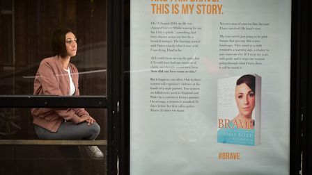 Acid attack victim Adele Bellis by the bus stop where she was attacked with a giant poster advertisi