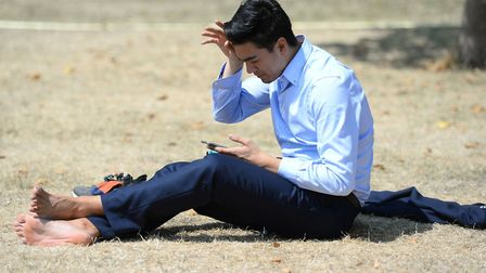 A man sits on the dry grass in the heat. Picture: PA IMAGES.