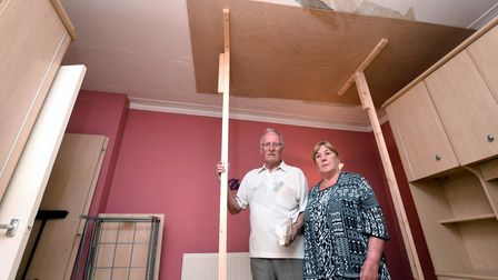 Michael and Elizabeth Kelly stand in their bedroom with the temporary ceiling brace above where thei