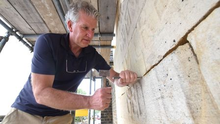 Restoration work on the West Front of St Augustine's Church, Archway Road. Conservator Tim removes t