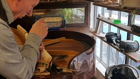 Desmond Gentle from Camden Piano Rescue mending the Challen grand piano that he will be taking to t