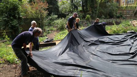 Volunteers from the Friends of Parkland Walk help lay the lining for the new pond. Picture: Stephen
