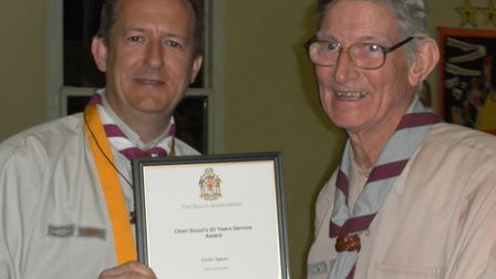 Les (right) receiving an award for 60 years service in 2012 from the then district commissioner Alan