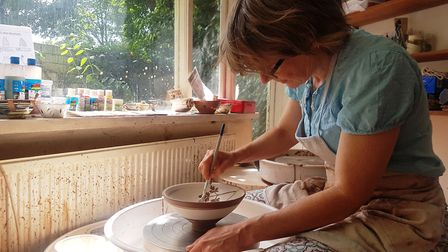 Matilda paints a bowl on a pottery wheel in the workshop