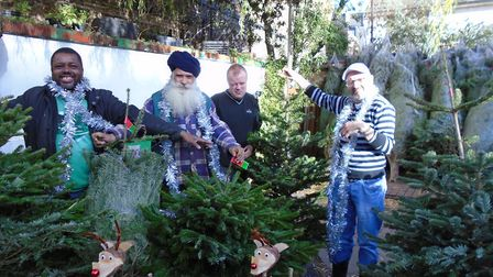 Volunteers Stephen, Singh, Tony, and Steven show off Mill Lane Garden Centre newly-delivered Christm