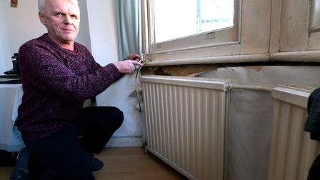 James Gosling of Sumatra Road shows the damp behind his radiators. Picture: Polly Hancock