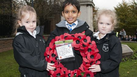 Emma,Nathan and Summer, four-year-old pupils from Hampstead Hill School, lay down a wreath at Hampst