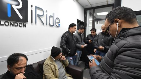 Drivers inside the iRide office where they are told the owner is not there. They phone him to talk a