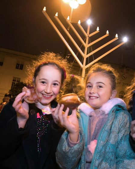 Girls eating Hannukah doughnuts at the Christmas lights switch on. Picture: Hackney Council/ Gary Ma
