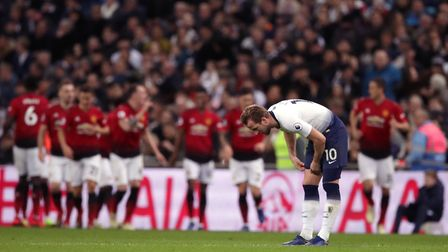 Tottenham Hotspur's Harry Kane appears dejected as Manchester United players (background) celebrate