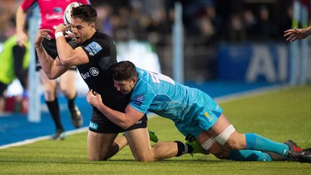 Saracens Sean Maitland gets a backwards pass away over his head under the challenge of Worcester War