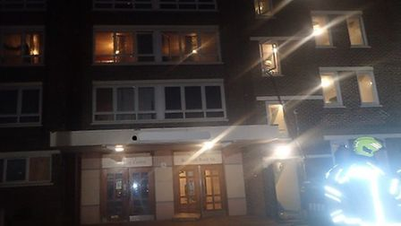 Firefighters rescue a woman from a second floor flat after a fire on Birkbeck Road, Hornsey. Picture