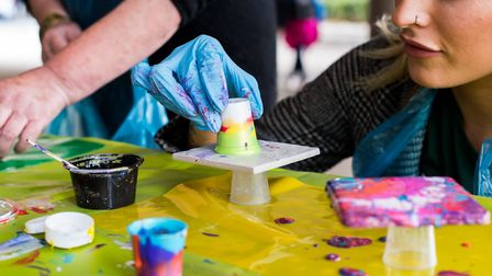 An eager partipant tries paint pouring in Swiss Cottage. Picture: Sarah Kennard