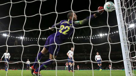 Tottenham Hotspur goalkeeper Paulo Gazzaniga makes a save, tipping the ball onto the post from Arsen