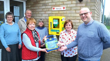Anne Everitt receiving the defibrillator on behalf of Pakefield Church PCC from Jayne Biggs and Rob