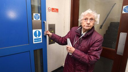 Bernadette McCarthy, 87. struggles to open one of the heavy fire doors which is supposed to open aut