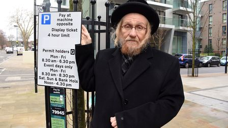 Cllr Aron Klein with one of the parking notices that includes the restrictions on bank holidays on W