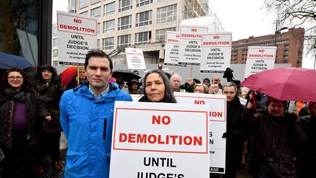 Save Swiss Cottage campaigners gather in the rain to opposed the demolition of 100 Avenue Road befor