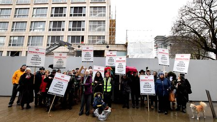 Protesters opposing the demolition of 100 Avenue Road stand with placards in front of the site while