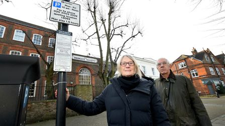 Elspeth Clements and Michael Hammerson stand next to a sign with Highgate's current parking hours. P