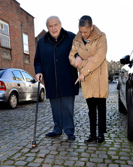 Lord Peter Eden is helped across the uneven cobbles on Fairfax Place, NW3 by PA Annette Whitney. Pic