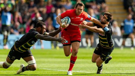 Saracens' Alex Goode breaks through the challenge of Cobus Reinach and Courtney Lawes at Northampton