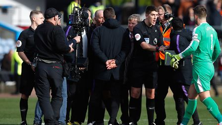 Tottenham Hotspur manager Mauricio Pochettino (centre) and his staff speak to referee Mike Dean and