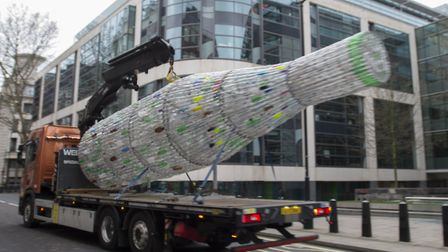 A 29ft plastic bottle designed by Lulu Quinn, delivered by Greenpeace to Michael Gove, is removed.