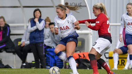 Tottenham Hotspur Ladies' Rianna Dean looks to keep the ball from a Manchester United Women's oppone
