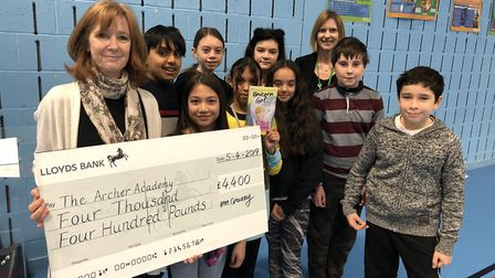 Local children's author Anne-Marie Conway presents a cheque for £4,400 to Archer Academy for their n