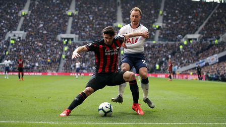 Huddersfield Town's Christopher Schindler (left) and Spurs playmaker Christian Eriksen battle for th