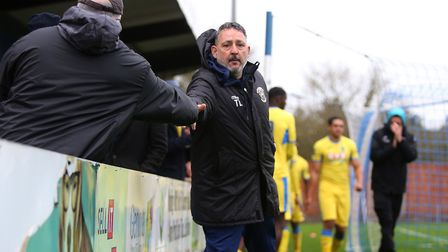 Haringey Borough manager Tom Loizou shakes hands with a fan after the final whistle at Bishop's Stor