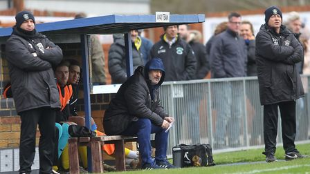 Tom Loizou looks on from the dugout while Haringey Borough coach Thomas O'Donoghue stands during the