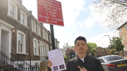 Eric Luk Man Hon with the PCN issued to him next to the red sign ahead of the bus gate