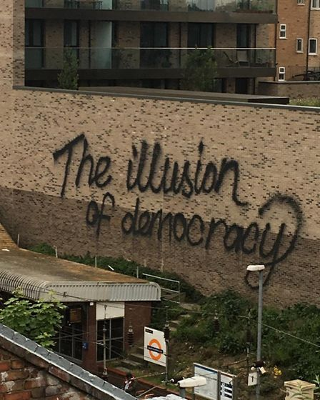 The graffiti on the side of the Fifty Seven East development towering over Dalston Kingsland's westb